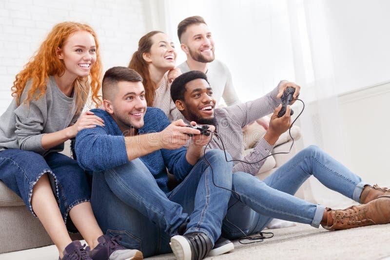 Przyjaciele bawić się gra wideo w domu, mieć zabawę obrazy stock