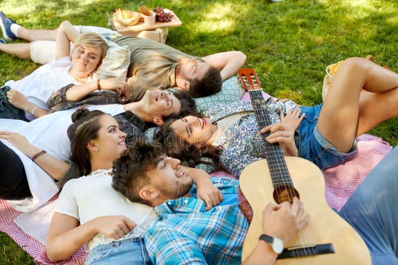 Przyjaciele bawić się gitarę i chłodzi przy lato parkiem zdjęcie stock