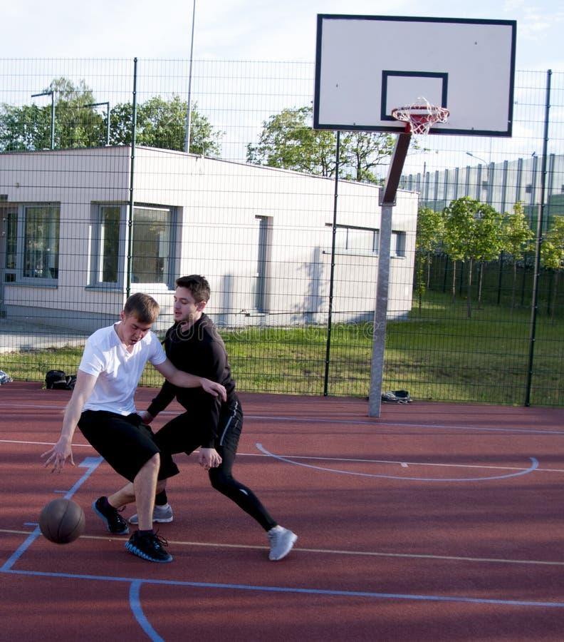 Przyjaciele bawić się uliczną koszykówkę zdjęcia royalty free