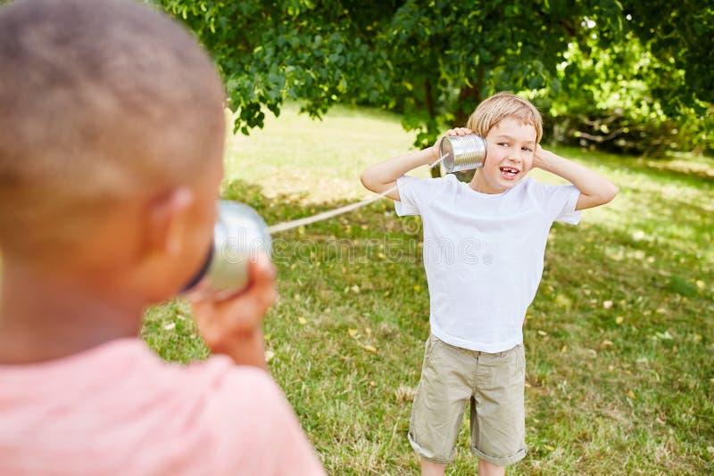 Przyjaciele bawić się w parku z blaszaną puszką telefonują fotografia stock