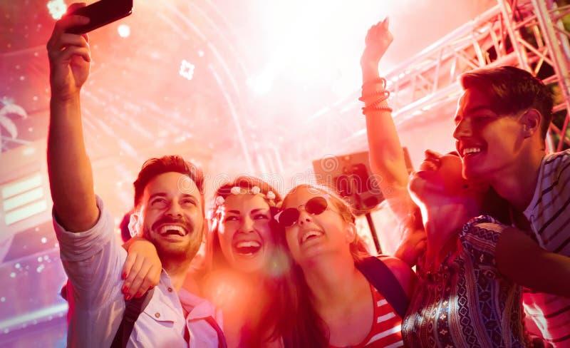 Przyjaciele bawi się w klubie przy nocą obraz stock