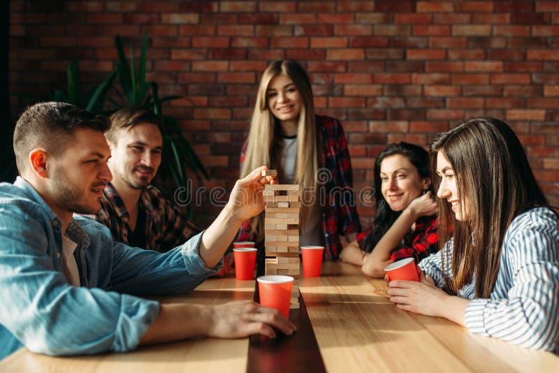 Przyjaciele bawi? si? sto?ow? gr?, selekcyjna ostro?? na wierza zdjęcia royalty free