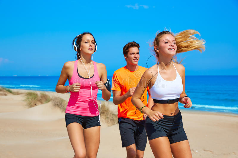 Przyjaciele biega na plaży szczęśliwej w lecie zdjęcia royalty free