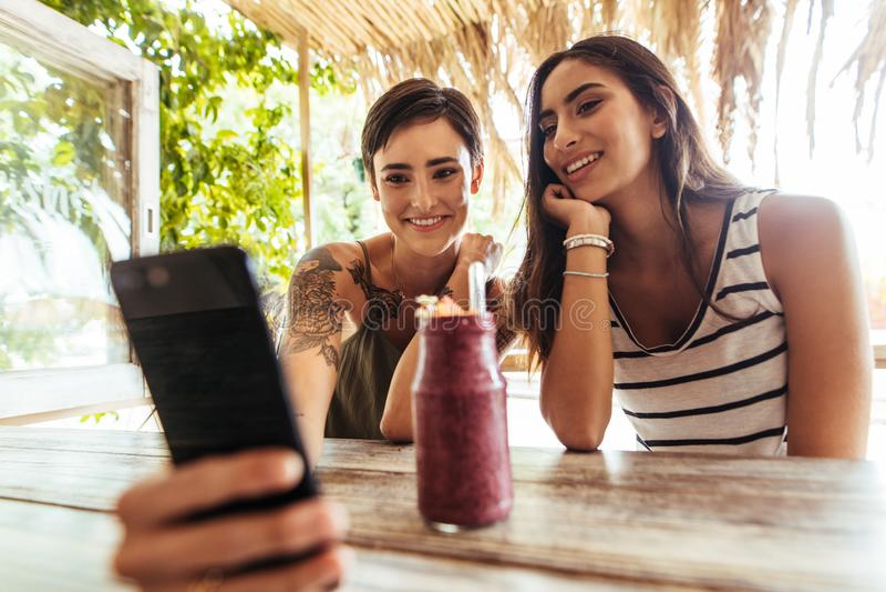 Przyjaciele bierze selfie z smoothie na stole fotografia stock