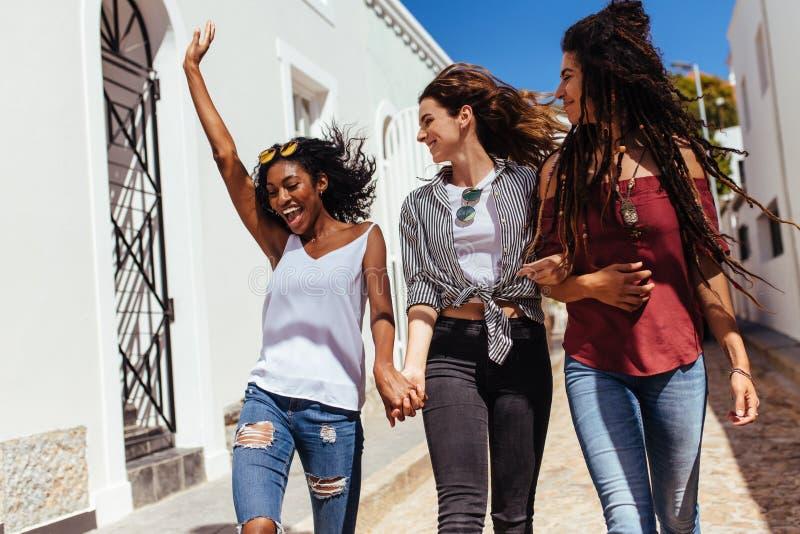 Przyjaciele chodzi na ulicie jest ubranym modnych ubrania fotografia royalty free