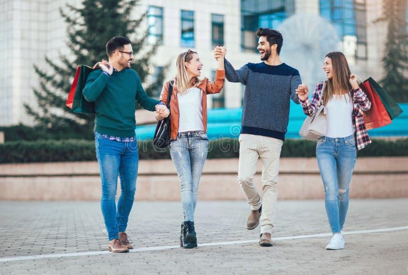 Przyjaciele Chodzi Wzdłuż ulicy Z torba na zakupy zdjęcie stock