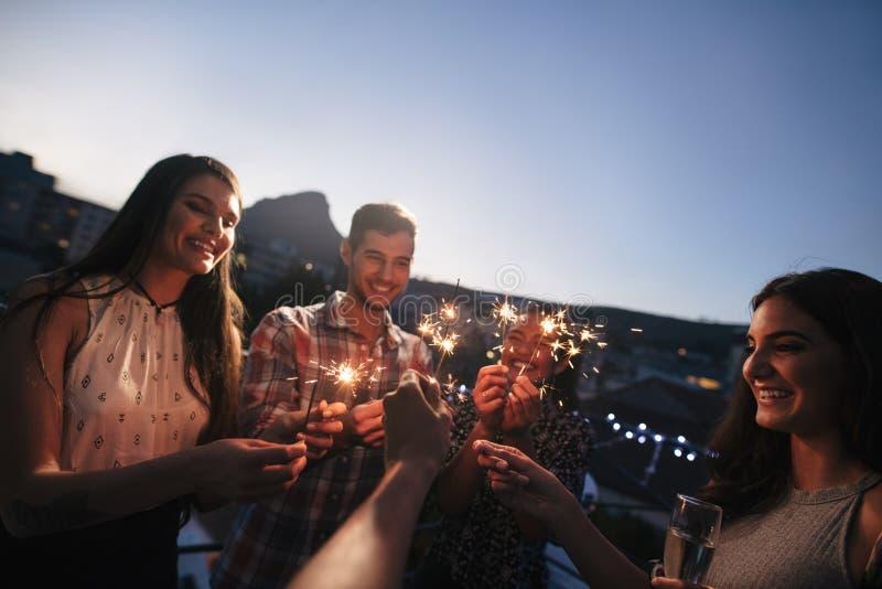 Przyjaciele cieszy się dachu przyjęcia z sparklers obraz stock