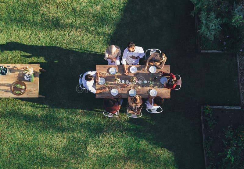 Przyjaciele cieszy się posiłek przy plenerowym przyjęciem w podwórku obrazy stock