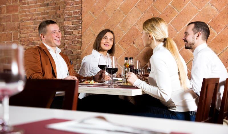Przyjaciele cieszy się wyśmienicie posiłek w kraj restauraci zdjęcie royalty free