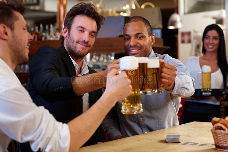 Przyjaciele clinking z piwnymi kubkami w pubie zdjęcia royalty free