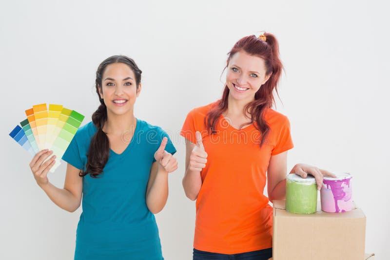 Przyjaciele gestykuluje aprobaty z swatches, pudełka i farby puszkami, obrazy stock