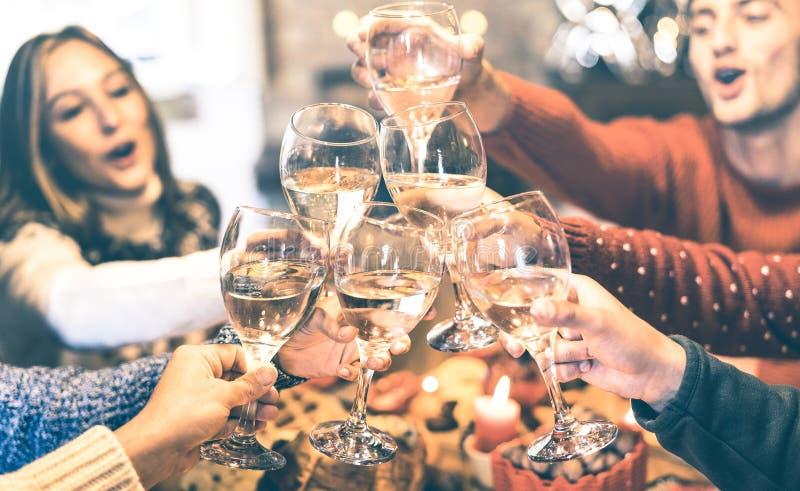 Przyjaciele grupują odświętności wina Bożenarodzeniowego wznosi toast szampańskiego obiadowego przyjęcia w domu fotografia stock