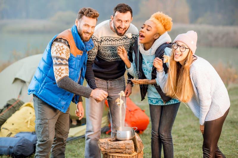 Przyjaciele je fondue outdoors w pulowerach obrazy royalty free