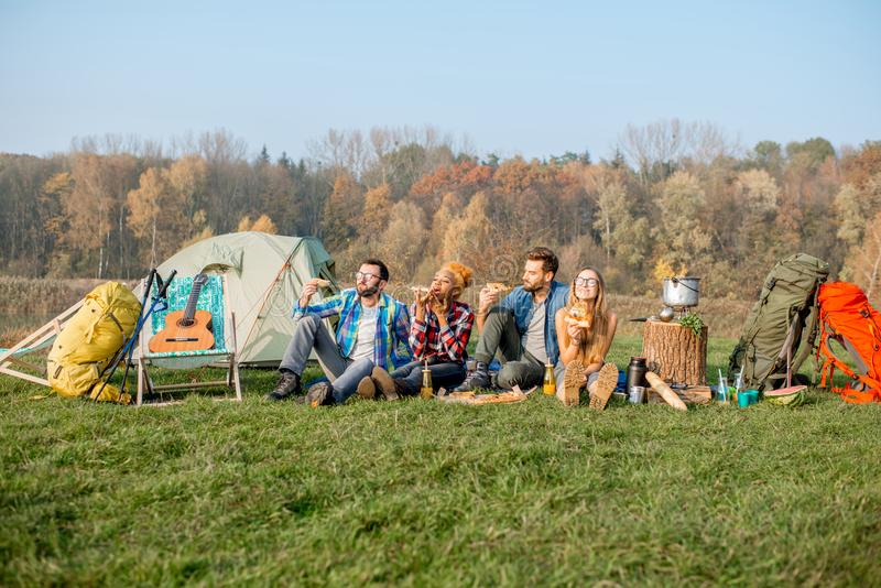 Przyjaciele je pizzę przy campingiem fotografia stock