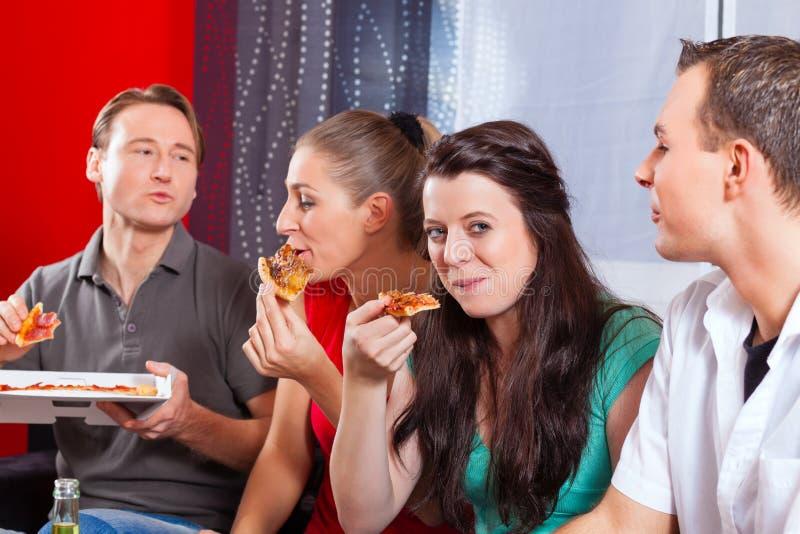 Przyjaciele je pizzę w domu obrazy royalty free