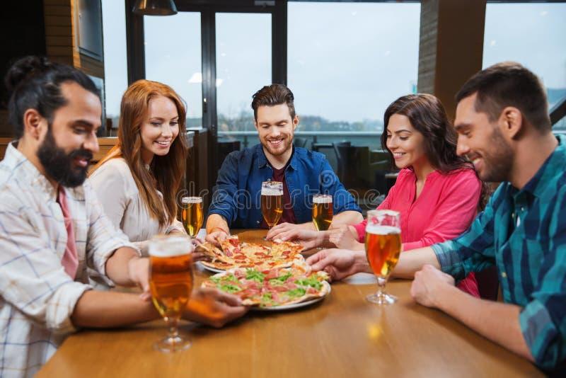 Przyjaciele je pizzę z piwem przy restauracją fotografia royalty free