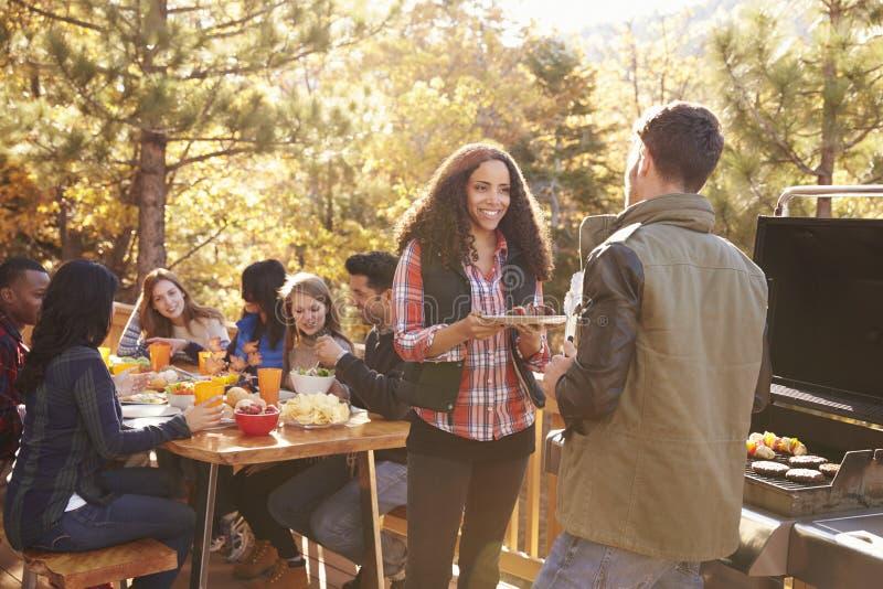 Przyjaciele jedzą przy stołem i dwa rozmową grillem przy grillem obraz royalty free