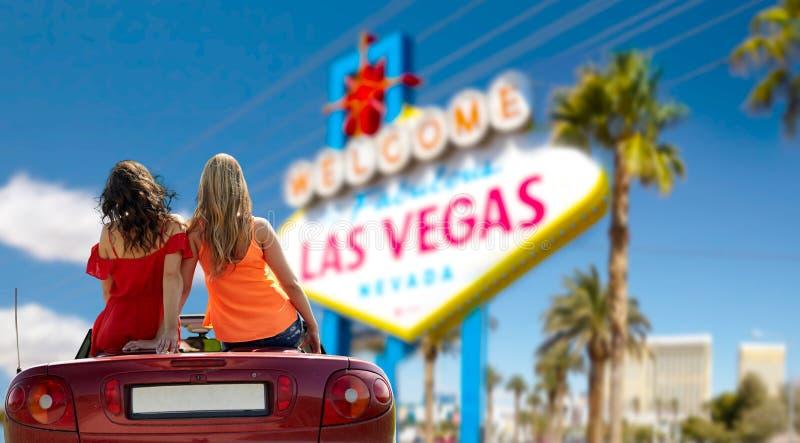 Przyjaciele jedzie w odwracalnym samochodzie przy lasami Vegas obraz royalty free