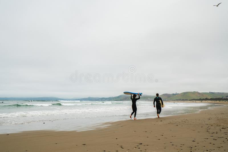 Przyjaciele jest ubranym w mokrych kostiumach z ich surfboards chodzi na pla?y obrazy royalty free