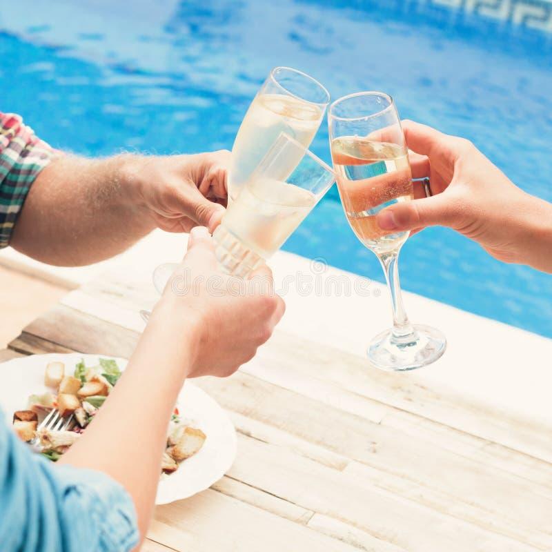 Przyjaciele ma wino przy przyjęciem pływackim basenem zdjęcia royalty free