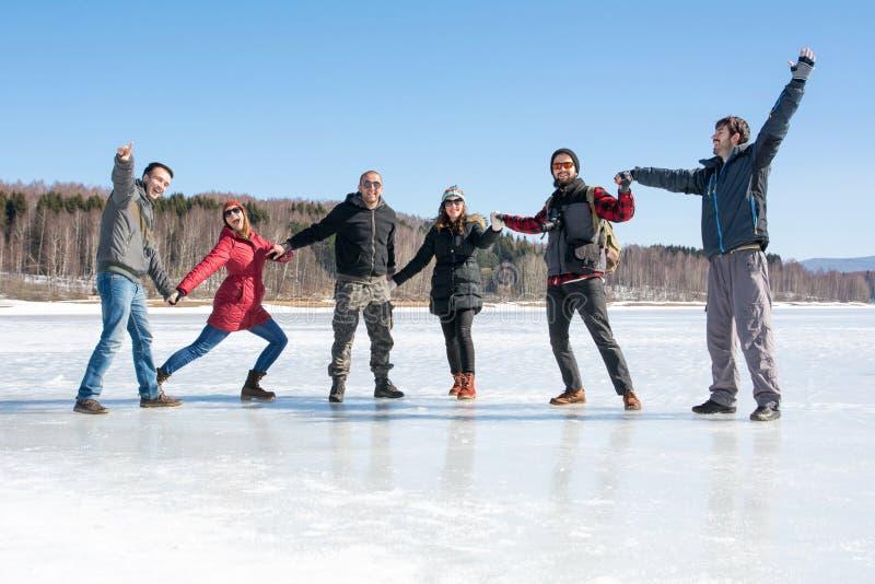 Przyjaciele ma zabawę na zamarzniętym jeziorze zdjęcia royalty free