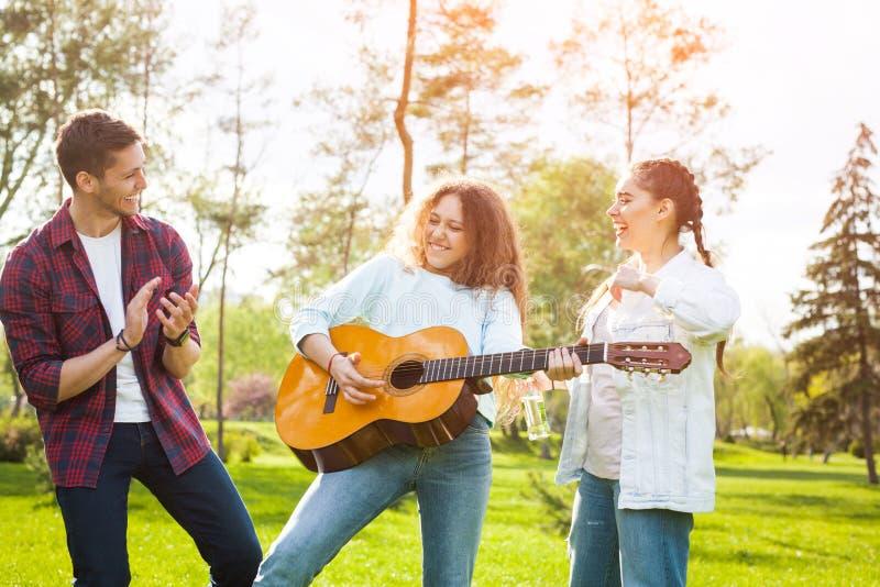 Przyjaciele ma zabawę w parku z gitarą zdjęcie royalty free