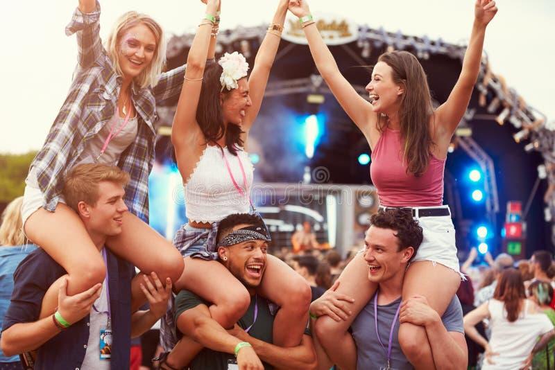 Przyjaciele ma zabawę w tłumu przy festiwalem muzyki zdjęcia royalty free