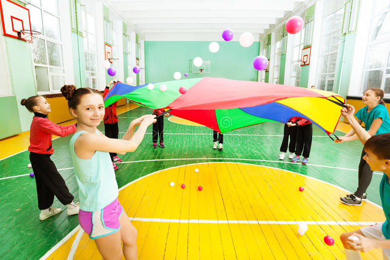 Przyjaciele macha spadochron z piłkami w sport sala obrazy royalty free