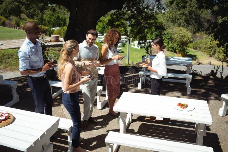 Przyjaciele oddziała wzajemnie podczas gdy kelnerki porci jedzenie fotografia royalty free