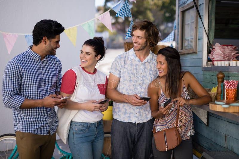 Przyjaciele oddziała wzajemnie podczas gdy używać telefon komórkowego przy kontuarem obraz royalty free