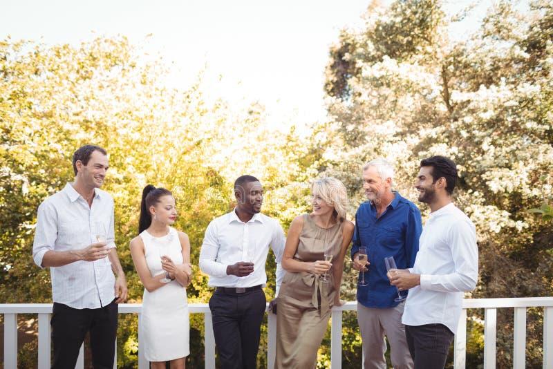 Przyjaciele oddziała wzajemnie z each inny podczas gdy mieć szampana w balkonie zdjęcia stock