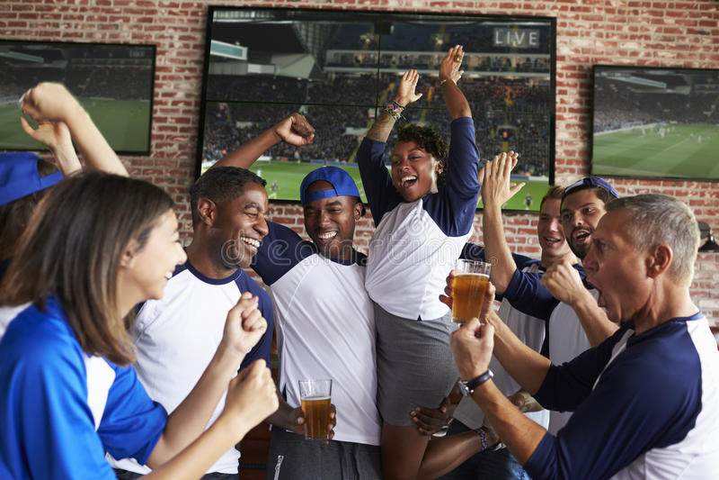 Przyjaciele Ogląda grę W sporta barze Na ekranów Świętować obraz royalty free