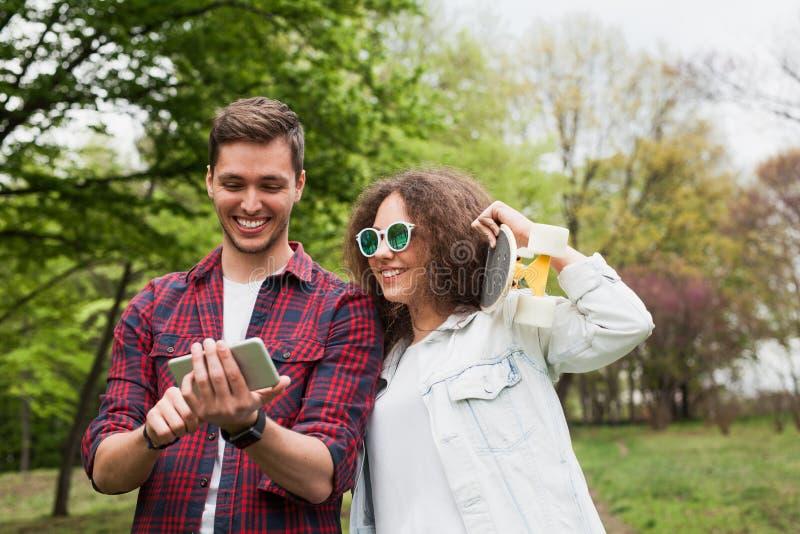 Przyjaciele ogląda smartphone na parku zdjęcie stock