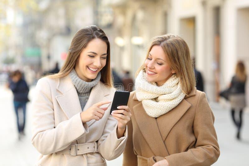 Przyjaciele ogląda telefon zawartość w zimie na ulicie zdjęcie royalty free