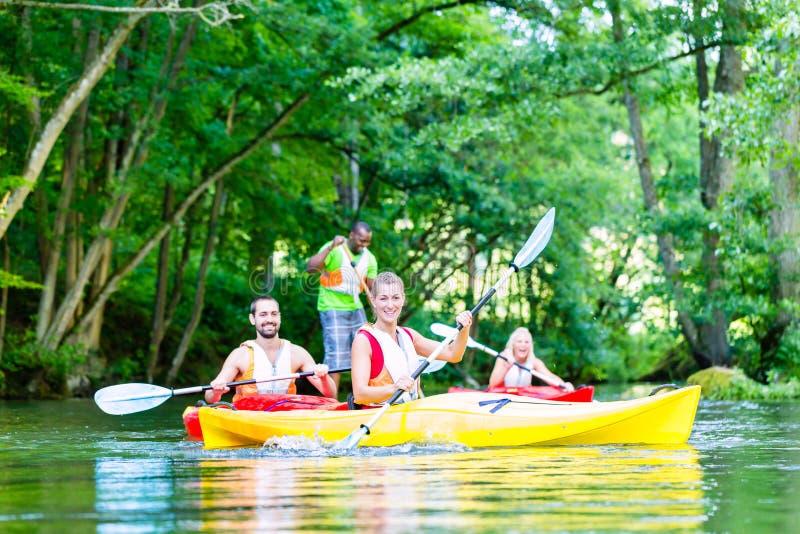 Przyjaciele paddling z czółnem na lasowej rzece obraz royalty free