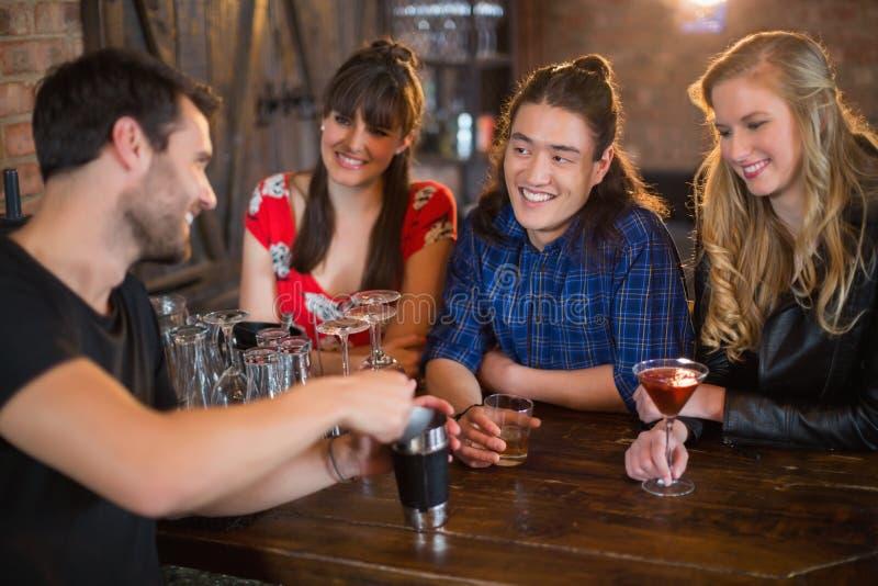 Przyjaciele patrzeje barmanu robi napojom w pubie zdjęcia royalty free
