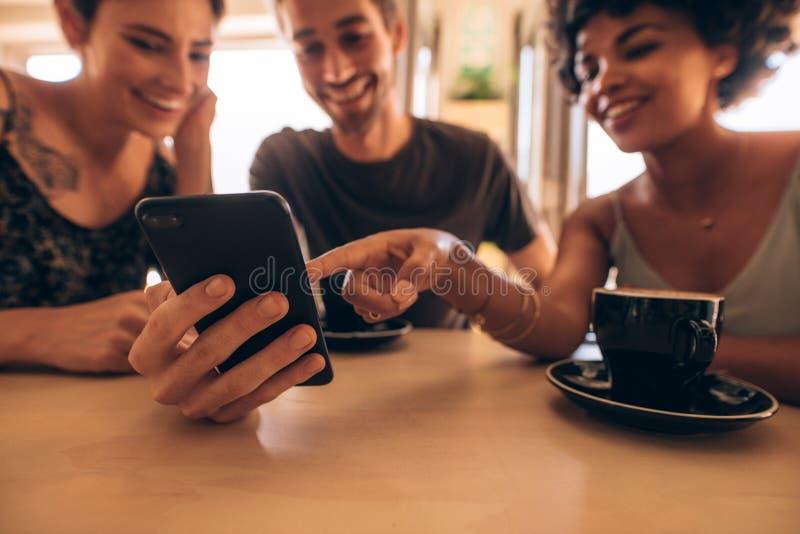 Przyjaciele patrzeje mądrze telefon w kawiarni obrazy royalty free