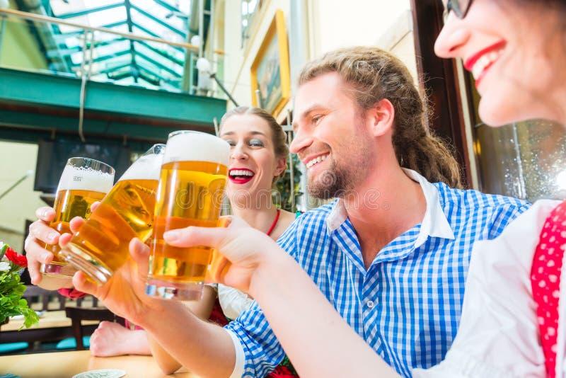 Przyjaciele pije piwo w Bawarskiej restauraci lub pubie obrazy stock