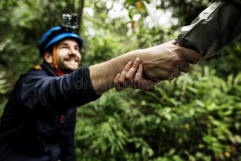Przyjaciele pomaga each inny podczas gdy trekking zdjęcie stock
