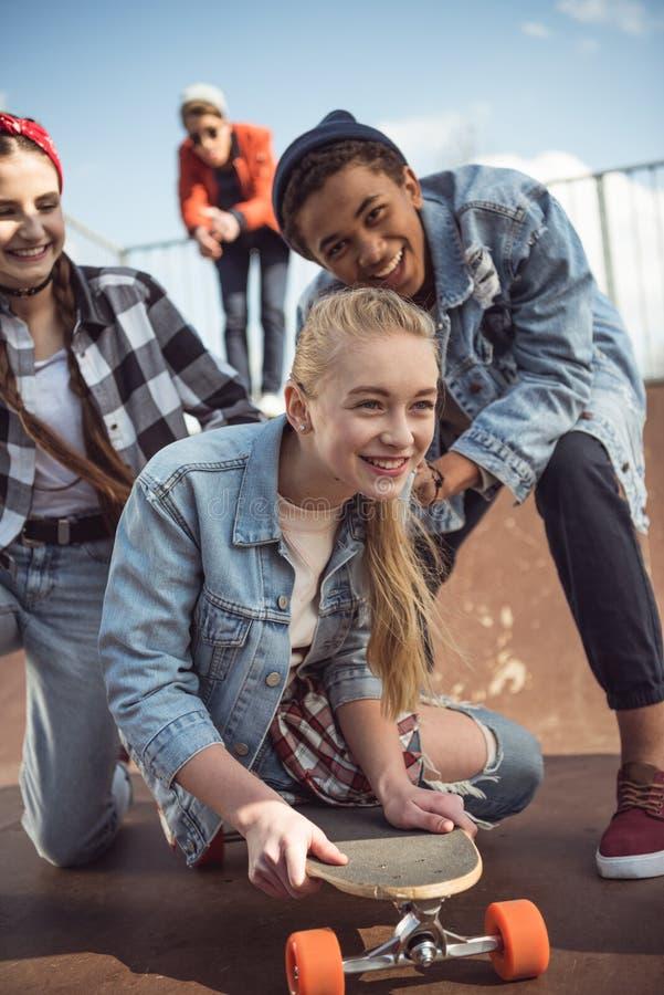 Przyjaciele pomaga elegancki modniś dziewczyny jazdy deskorolka obraz royalty free