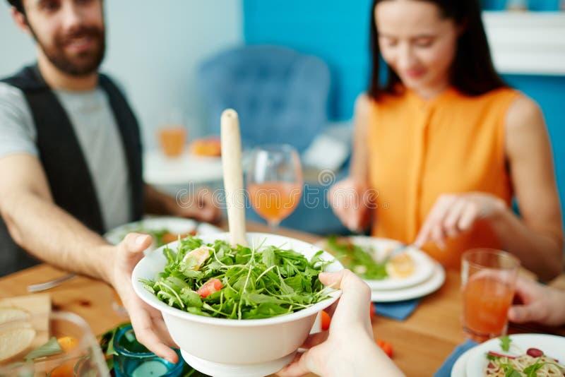 Przyjaciele przechodzi zielonej sałatki podczas gdy jedzący wpólnie obrazy royalty free