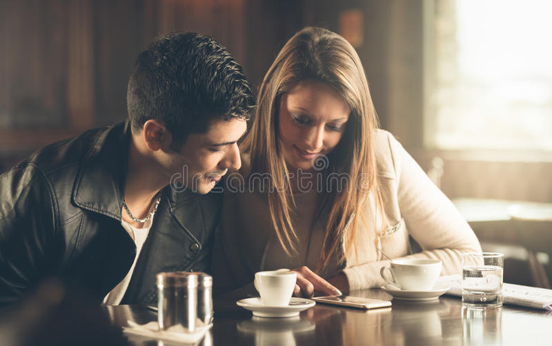 Przyjaciele przy kawiarnią używać telefon komórkowego obrazy stock
