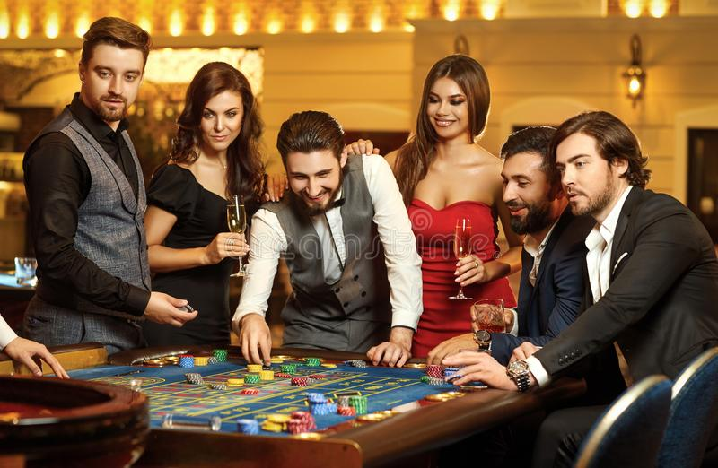 Przyjaciele robią zakładom gambiling przy ruleta stołem w kasynie fotografia royalty free