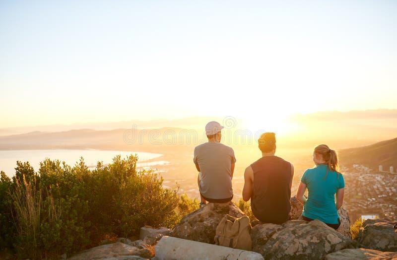 Przyjaciele siedzi na halnym śladzie ogląda wschodu słońca togethe obrazy stock