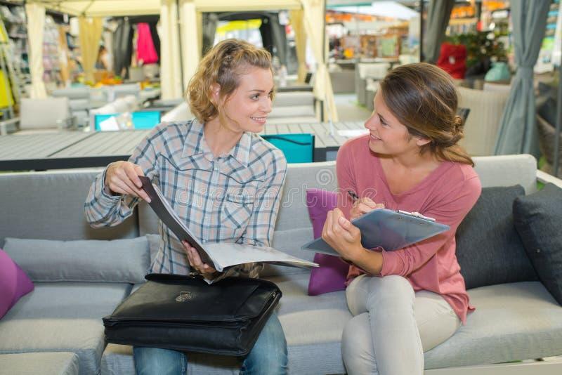 Przyjaciele sprawdza broszurkę w sklepie zdjęcia stock
