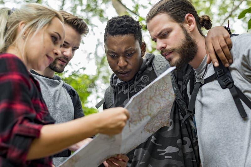 Przyjaciele sprawdza mapę dla kierunku zdjęcia royalty free