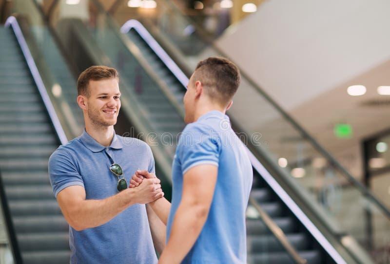 Przyjaciele trząść ręki w zakupy centrum handlowym zdjęcie royalty free