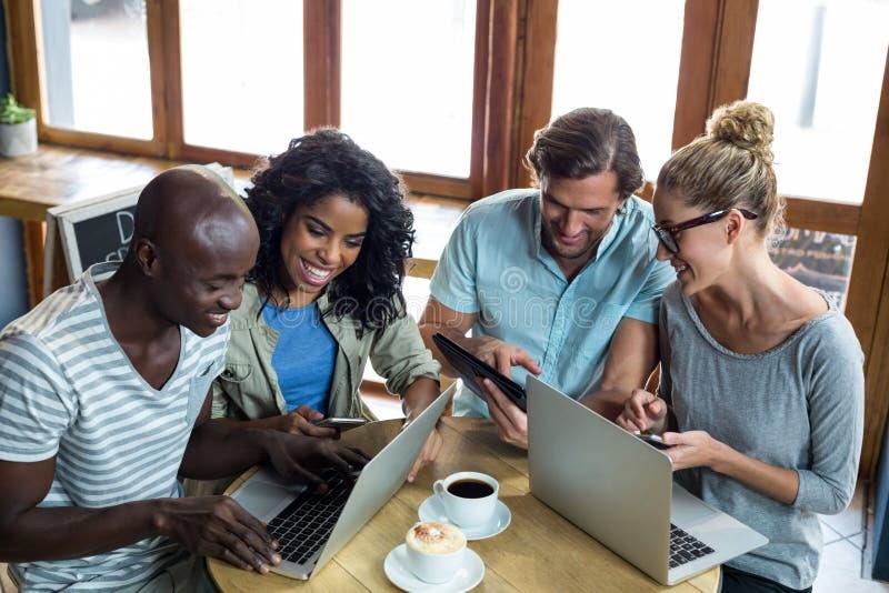 Przyjaciele używa laptop, telefon komórkowego i cyfrową pastylkę, podczas gdy mieć kawę obraz stock