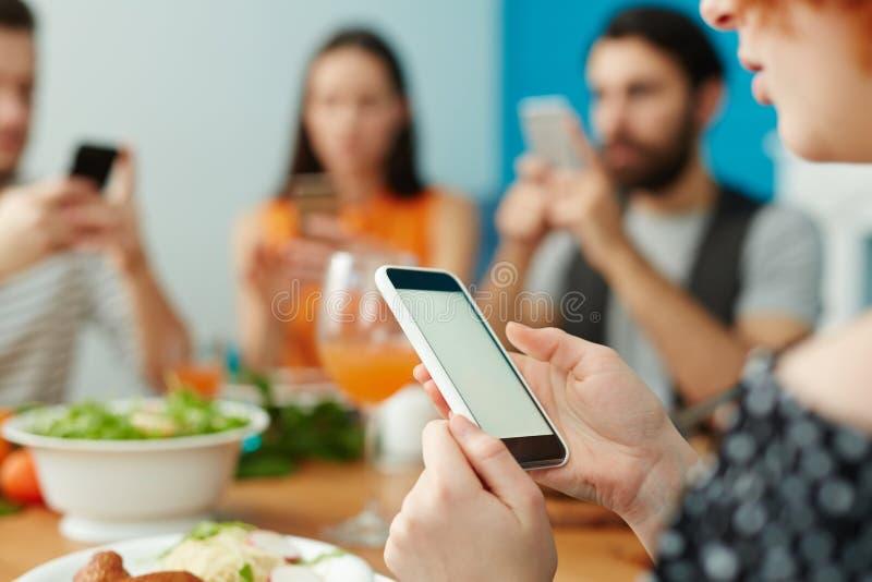 Przyjaciele używa smartphones podczas gdy jedzący wpólnie fotografia royalty free
