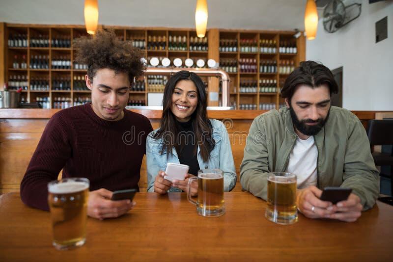 Przyjaciele używa telefon komórkowego na stole obraz stock